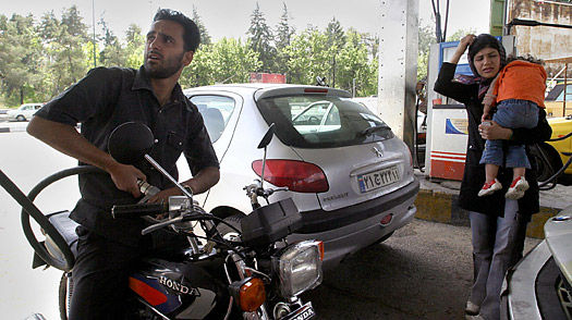 An Iranian pumps gasoline into his motorbike at a gas station north of Tehran