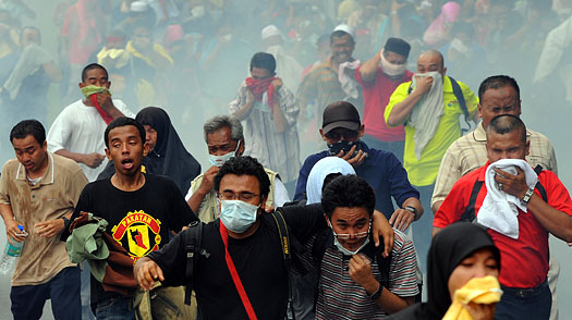 Demonstrators flee as Malaysian anti-riot police fire tear gas shells near Merdeka Square in Kuala Lumpur on August 1, 2009