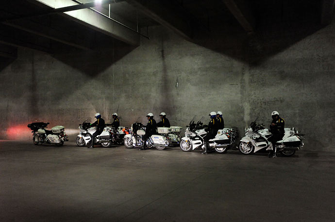 Police escorting the Presidential motorcade wait in an underground parking lot as President Obama gives a speech during the