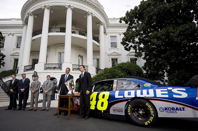 US President Barack Obama (second from right) stands with NASCAR Sprint Cup Champion Jimmie Johnson (right) and his car after delivering