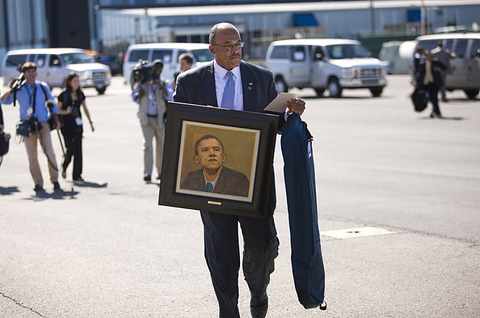 A member of the White House Residence Staff carries a gift for President Obama to Air Force One at Albany International Airport in New York.