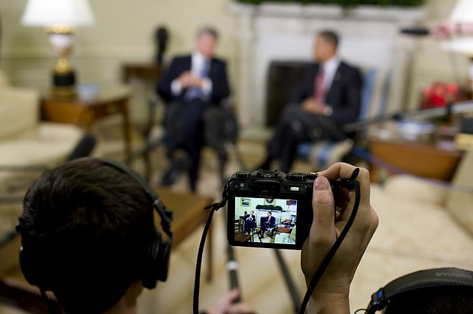 A journalist videotapes President Obama meeting with Canada's Prime Minister Stephen Harper in the Oval Office.