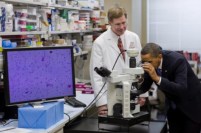 President Obama looks at brain cells during a tour of an oncology laboratory at the National Institutes of Health in Bethesda, Maryland.