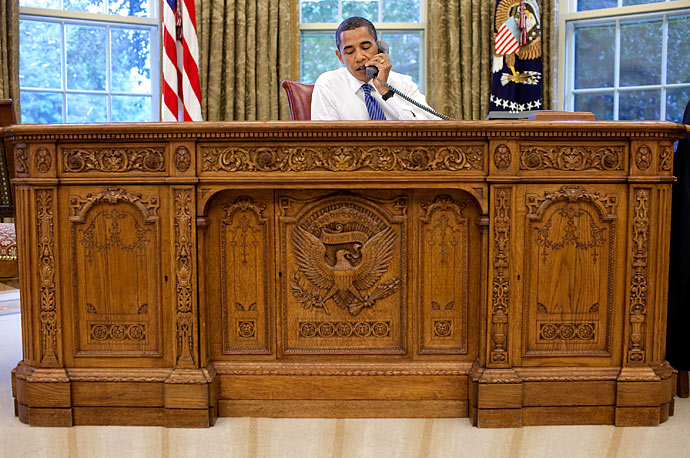 President Obama sits behind the Resolute Desk in the Oval Office during a conference call.