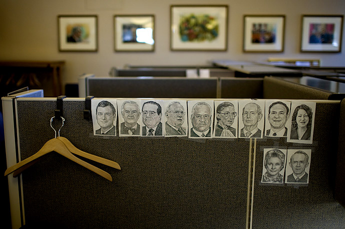 Etchings of current and former Supreme Court Justices are posted in a cubicle in the press room at the Supreme Court in Washington, DC.