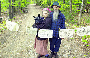 Author Carolyn Chute holding her dog, Margaret, stands with her husband, Michael Chute at the end of their driveway by their home in Parsonsfield, Maine