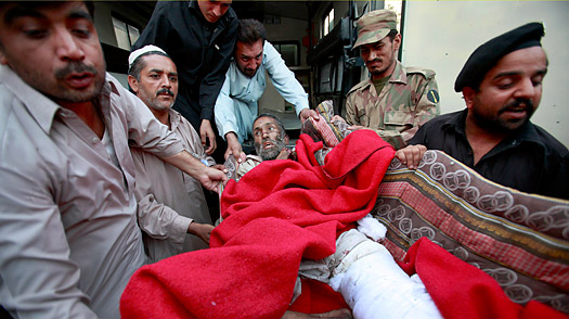 A soldier, policeman and hospital staff move a man, who was injured in a bomb attack in Shangla district, to the Lady Reading hospital in Peshawar October 12, 2009.