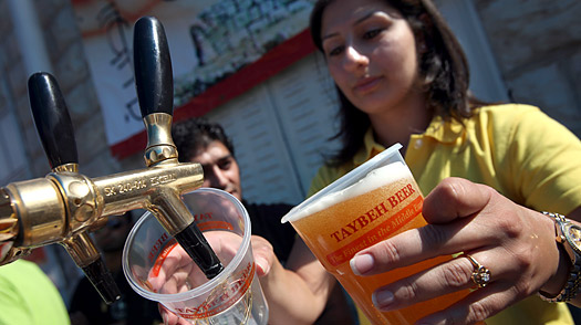 A vendor draws pints of Taybeh Golden draught beer during the Palestinian brewery's annual Oktoberfest on October 3, 2009 in Taybeh in the West Bank.