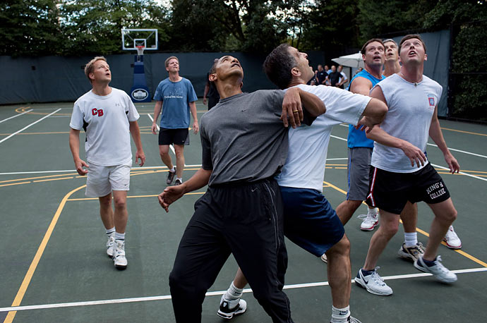 President Obama, along with Cabinet Secretaries and Members of Congress, watch a shot during a basketball game on the White House court.