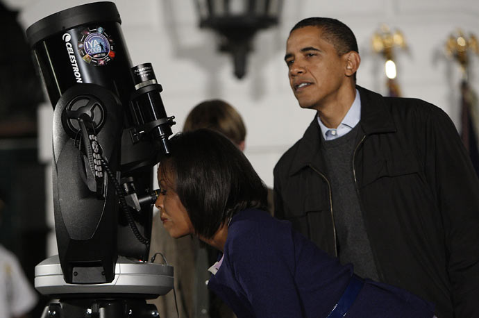 President Obama looks over the shoulder of his wife first lady Michelle Obama as she looks through a telescope on the South Lawn of the White House.