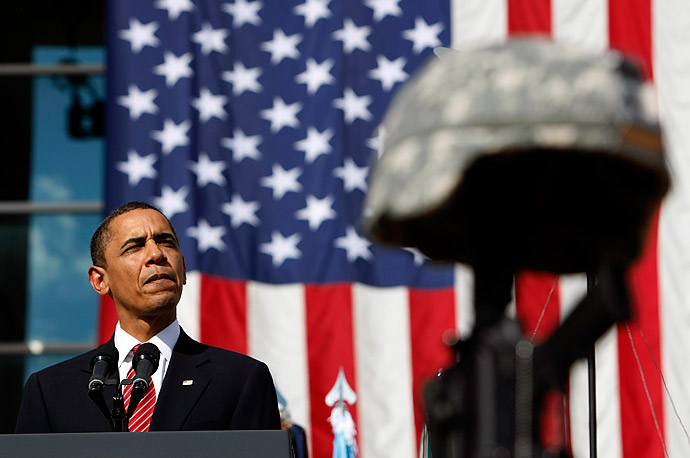 President Barack Obama speaks behind the helmets and rifles of the fallen soldiers during the III Corps and Fort Hood Memorial Ceremony held to honor the victims of the shootings on the Fort Hood Army post.
