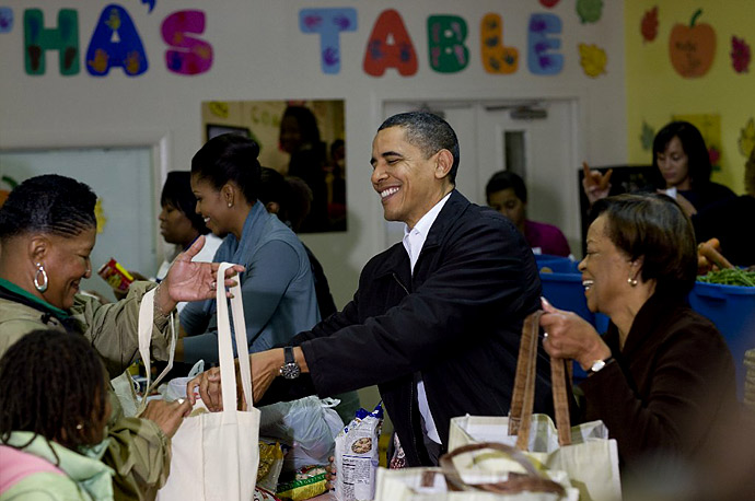 President Obama fills a bag with a Thanksgiving day pumpkin pie alongside first lady Michelle Obama during their visit to Martha's Table, a community-improvement organization for the underprivileged in Washington.