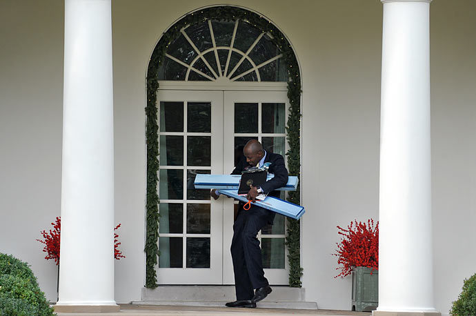 President Obama's personal aide Reggie Love, his arms laden with track lights and dimmers, struggles to open a door to the Oval Office after returning from Obama's speech at a Home Depot in Alexandria, Virginia.