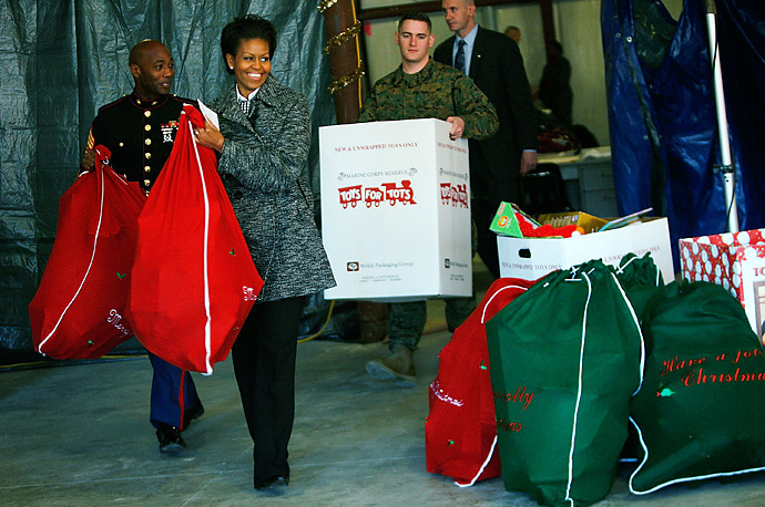 Michelle Obama carries a bag of toys which have been donated by White House Executive Office staff to Marine Toys for Tots, in Stafford, Virginia