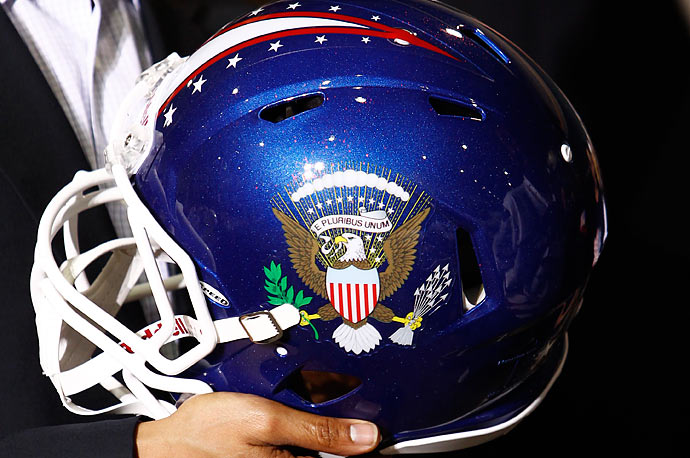 President Barack Obama holds a football helmet emblazoned with the Presidential Seal during his visit to a Riddell manufacturing facility in Elyria, Ohio.