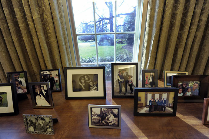 Family photos appear on President Obama's desk in the Oval Office.
