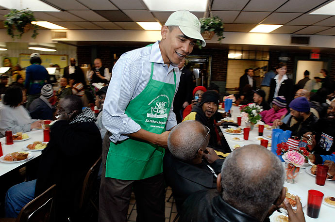 President Barack Obama greets people while volunteering at the So Others Might Eat dining room for the homeless in Washington, in honor of Martin Luther King Jr. Day.