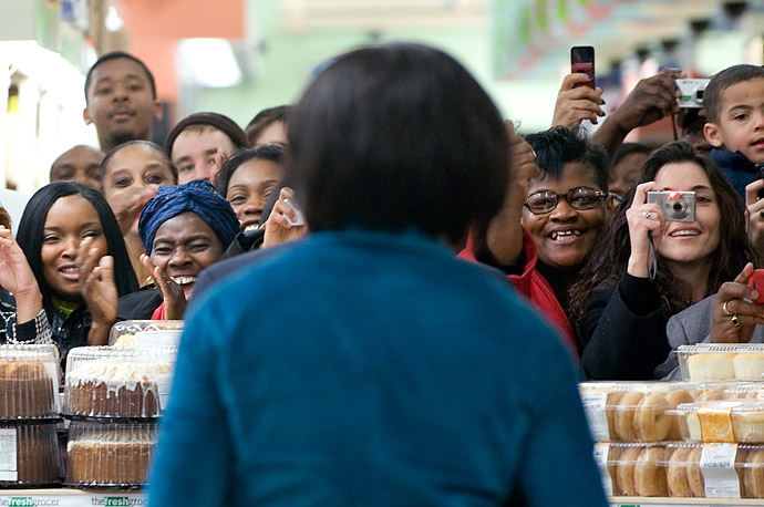 Store patrons greet U.S. First Lady Michelle Obama, center, as she touring the Fresh Grocer supermarket, in Philadelphia, Pennsylvania.