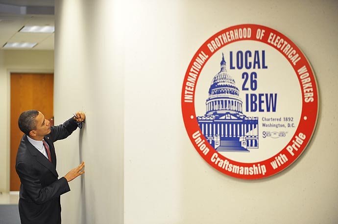 President Obama signs his name on the wall during a visit to the International Brotherhood of Electrical Workers Local 26 headquarters in Lanham, Maryland.