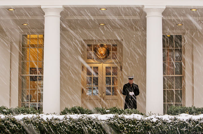 A Marine stands sentry outside the White House as snow blankets the U.S. capital.
