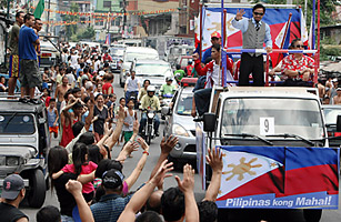 Filipino welterweight boxing champion Manny Pacquiao waves to supporters during a motorcade celebration in Manila