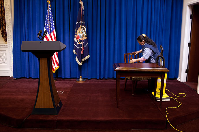 A custodian dusts and vacuums prior to President Barack Obama's Tax Deliquency Memorandum signing ceremony in the Eisenhower Executive Office Building of the White House.