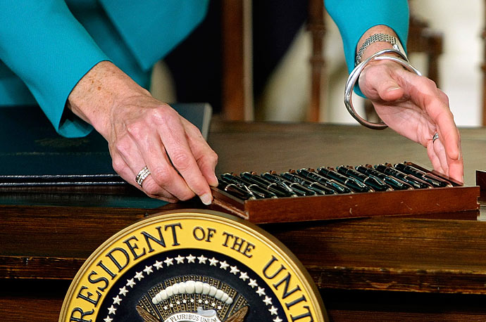 A White House staff member sets out the pens that President Barack Obama will use to sign the health care bill, Tuesday, March 23, 2010, in the East Room of the White House.