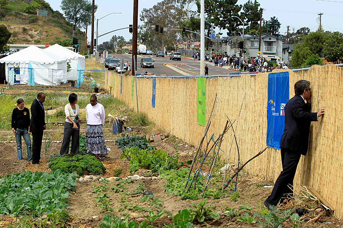 A secret service agent peeks through a fence as U.S. first lady Michelle Obama, third from left, visits the New Roots Community Farm in San Diego, California.