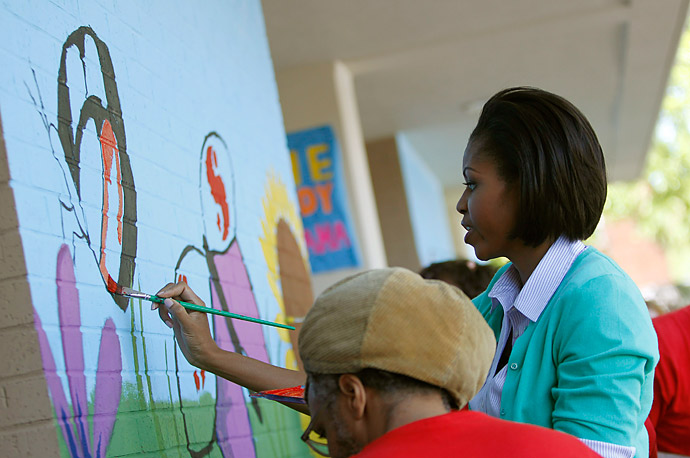 First lady Michelle Obama paints a mural featuring butterflies as she performs a public service event with the spouses of Congressional leaders at the Marie Reed learning center in Washington,