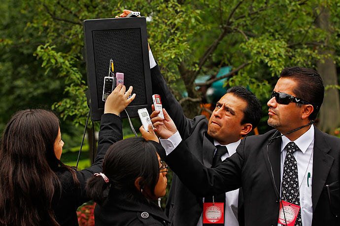 Members of the Mexican press hold audio recording devices against a speaker during a news conference with U.S. President Barack Obama and Mexican President Felipe Calderon in the Rose