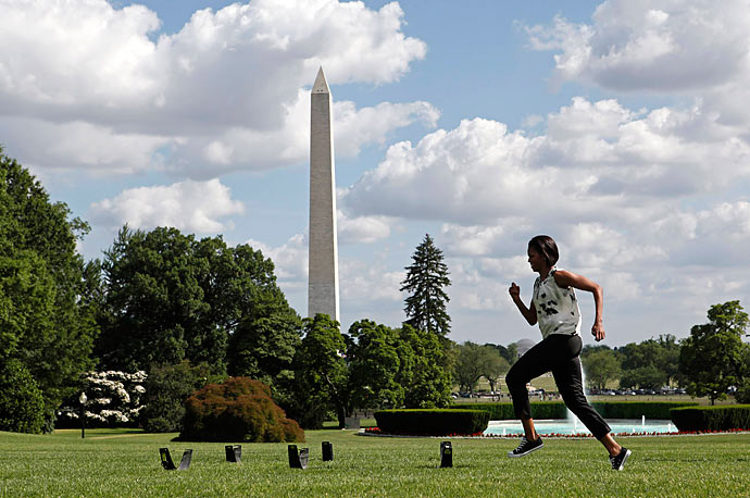 First lady Michelle Obama runs across the White House South Lawn during an event to promote physical activity.