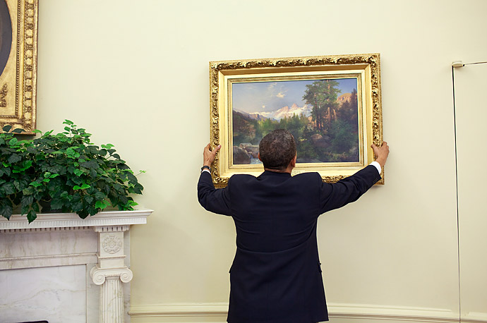 President Barack Obama straightens a painting in the Oval Office.