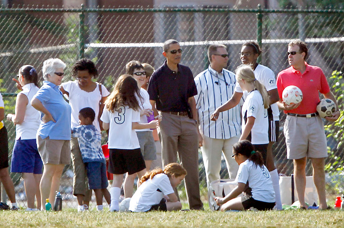 President Barack Obama, center, stands on the sidelines of the soccer field behind Rudolph Elementary School in Washington D.C. to watch his daughter, Malia, play soccer.