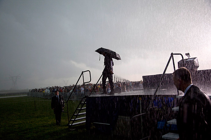 President Barack Obama walks off stage in the rain after urging the crowd to go to their cars, Monday, June 31, 2010, during a Memorial Day ceremony at Abraham Lincoln National Cemetery in