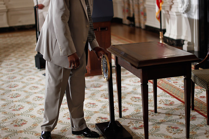 The seal of the President is adjusted before the signing of the Improper Payments Elimination and Recovery Act in a ceremony in the State Dining Room of the White House.