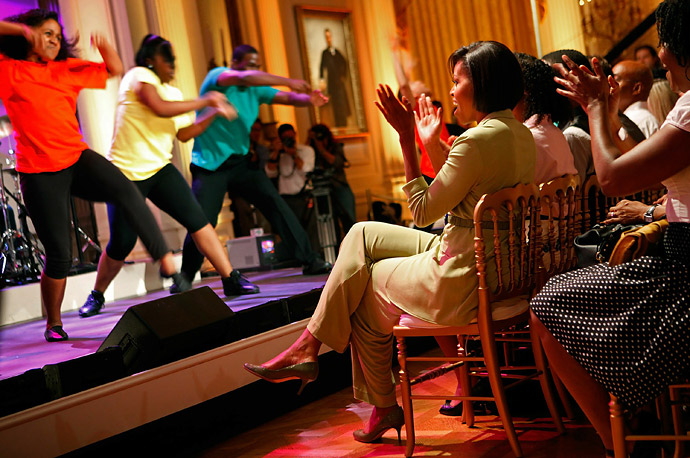 First Lady Michelle Obama applauds during a dress rehearsal of 20 dance students from Duke Ellington School of the Arts and the Joy of Motion Dance Center in the East Room of the White House.