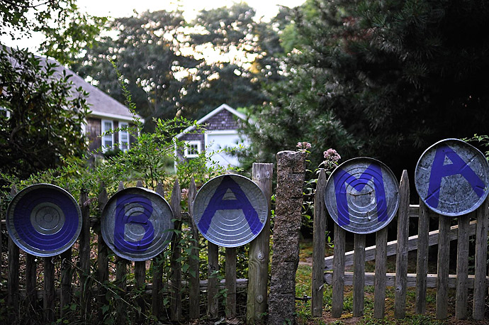 Painted rubbish bin lids adorn the fence of a home on Martha's Vineyard, where President Obama and his family are vacationing.