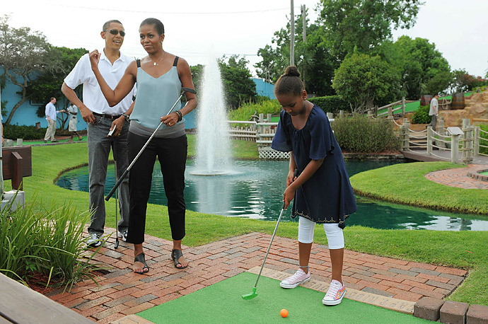 President Obama and First Lady Michelle watch their daughter Sasha putt during a round of mini golf in Panama City Beach, Florida.