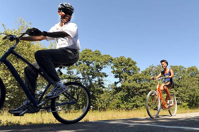 US President Barack Obama(L) smiles as he looks at the remote cameras set up by the press pool photographers as he rides his bicycle followed by his daughter Malia in West Tisbury on Martha's