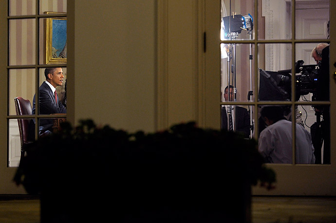 President Barack Obama, photographed from the Rose Garden, delivers a primetime televised address from the Oval Office of the White House to mark the the end of the combat mission in Iraq.