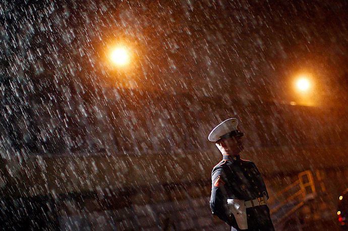 A Marine stands in the rain as he waits for the arrival of President Obama on the tarmac at John F. Kennedy Airport in New York City.