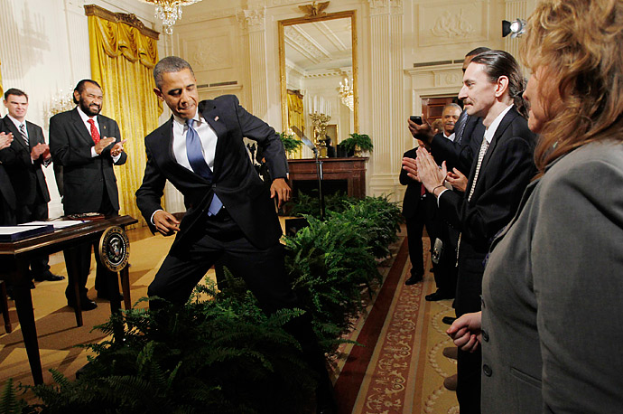 President Obama steps over a row of potted ferns as he meets members of the audience after signing the Small Business Jobs Act at a ceremony in the East Room of the White House.