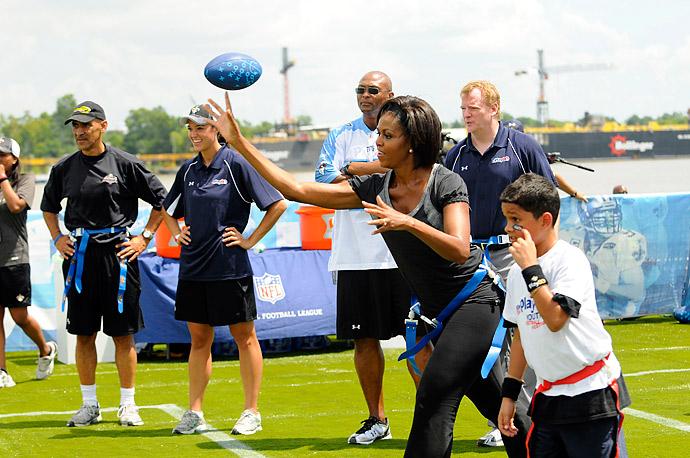 First lady Michelle Obama plays flag football with children, former NFL players and coaches during her