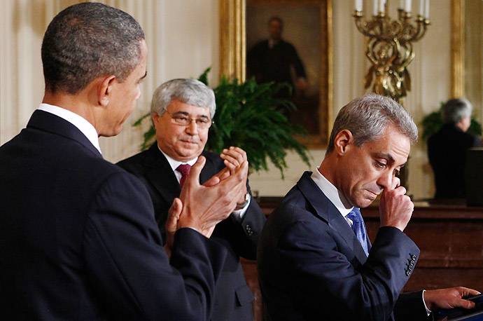 President Barack Obama, left, and newly named interim White House Chief of Staff Pete Rouse, second from left, applaud outgoing Chief of Staff Rahm Emanuel as he wipes away tears in the East Room at the White House in Washington D.C.