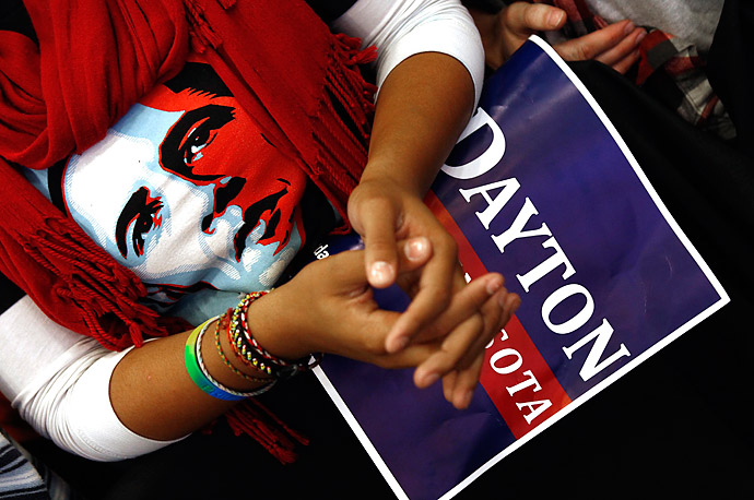 A woman wearing an Obama shirt listens as the President speaks in support of gubernatorial candidate Mark Dayton at a campaign rally in Minneapolis.