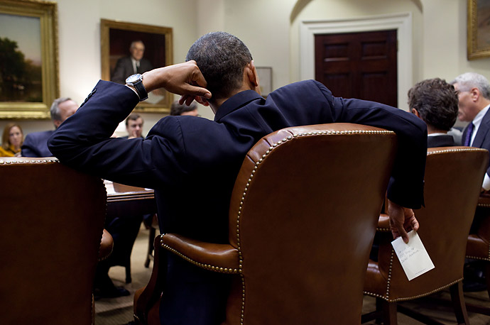 President Barack Obama holds a note from Personal Secretary Katie Johnson during the Economic Presidential Daily Briefing, in the Roosevelt Room of the White House.