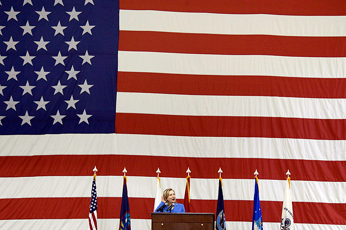 Secretary of State Hillary Clinton listens for cheers from US troops during an event at Andersen Air Force Base on the island of Guam . Clinton arrived for a brief stopover before heading to Vietnam