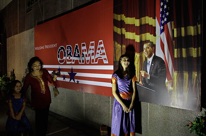 A woman makes her daughter pose for a photograph besides a poster of U.S. President Barack Obama in Calcutta, India. Obama is scheduled to visit India Nov. 6th-9th.