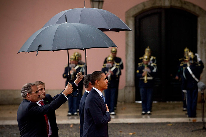 President Barack Obama listens to the American national anthem next to Portuguese President Anibal Cavaco Silva during the arrival ceremony for a NATO summit at the Belem National Palace in
