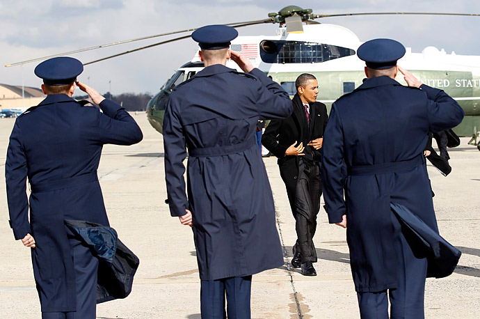 U.S. President Barack Obama pulls his coat closed as he boards Air Force One on a cold morning in Washington.
